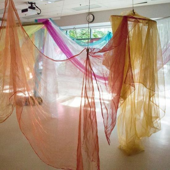 coloured translucent material in pink, yellow, orange and white hung from the ceiling