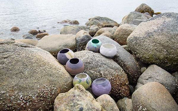 A number of pottery bowls outdoors sitting on rocks